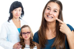 teen girl pointing at dental braces